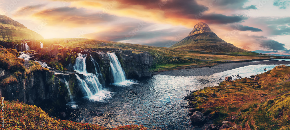 Fototapeta Amazing mountain landscape with colorful vivid sunset on the cloudy sky over the famous Kirkjufellsfoss Waterfall and Kirkjufell mountain. Iceland. popular location for landscape photographers.