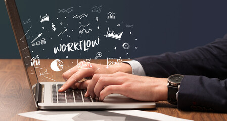 Businessman working on laptop with WORKFLOW inscription, modern business concept