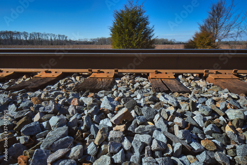 A railroad track with ties and ballast on a sunny day. Canvas Print