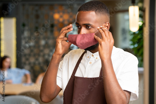 Young African man in uniform of waiter putting protective mask on his face #374541911