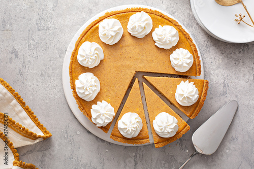 Fototapeta Pumpkin pie with whipped cream with slices taken out