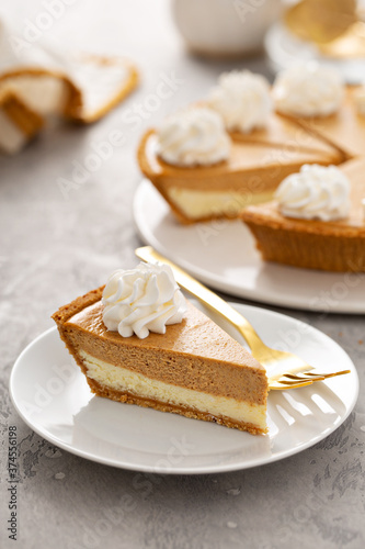 Obraz na plátně Slice of pumpkin pie with a cheesecake layer topped with whipped cream
