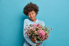 Portrait Of Romantic Young Woman Embraces Pretty Flowers, Gets Bouquet From Secret Admirer, Feels Touched, Stands With Eyes Closed, Wears Blue Clothing, Stands Indoor. Women And Holidays Concept.