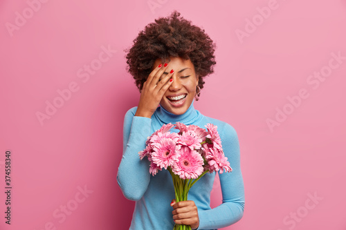 Overjoyed Afro American woman laughs out loudly, keeps palm on face, stands indo Fototapet