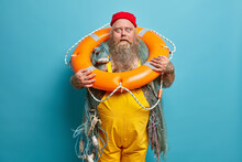Marine Profession. Stunned Bearded Seafarer Stares Has Bugged Eyes, Poses With Inflated Swim Ring, Wears Yellow Overalls, Isolated On Blue Background, Travels In Sailboat. Sailor Carries Lifebuoy