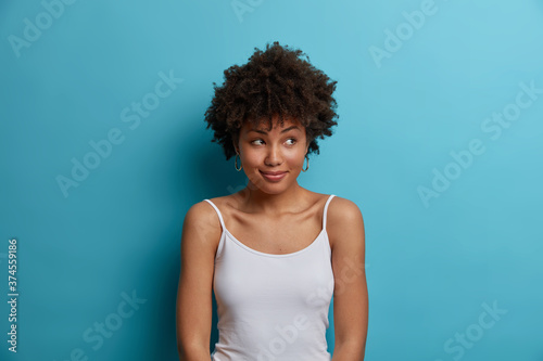 Photo Dreamy positive dark skinned woman with Afro hair looks aside, has pleasant smile on face, dressed in casual vest, notices something pleasant, poses against blue background