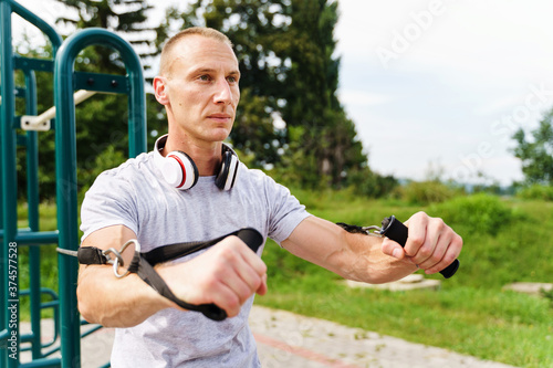 Stampa su Tela Adult caucasian man training outdoor in summer day - Male athlete using resistan