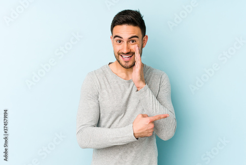 Tela Young caucasian man isolated on blue background saying a gossip, pointing to side reporting something