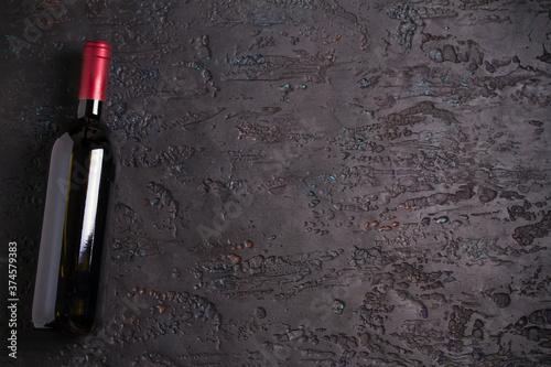 Fotografie, Tablou Bottle of red wine, wine glass on black background, copy space