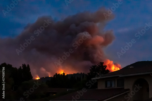 "The California ""River Fire"" of Salinas,  in Monterey County, ignited by dry lightning on August 16, 2020, fills the evening sky with smoke and flames as it burns close to houses on its first day."