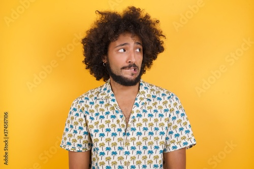 Fotografia, Obraz Photo of amazed  Young man with afro hair over wearing hawaiian shirt standing o