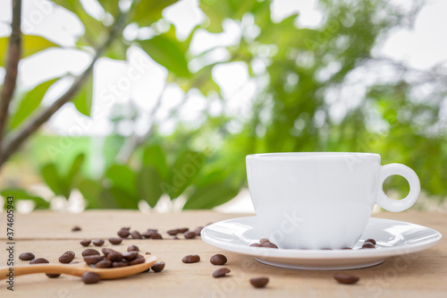 Fotografia A white coffee cup with a saucer and spoon is placed on a wooden plate on the landscape nature background