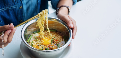 Photo Closeup image of a woman eating asian style instant noodle at home