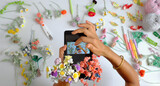shooting time handmade crochet product of female photographer, two hand hold tab and take photo from colorful flower artwork