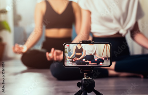 Obraz na płótnie Yoga online to live streaming on a smartphone, The fitness trainer teaches exercise so that the audience via the Internet for watching tutorial lesson at home