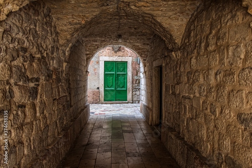 Obraz na plátne An alleyway in the old town of Kotor, Montenegro, with a green door at the end