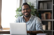 Head shot portrait smiling African American businessman wearing glasses sitting at work desk with laptop, excited freelancer looking at camera, happy student working on online research project