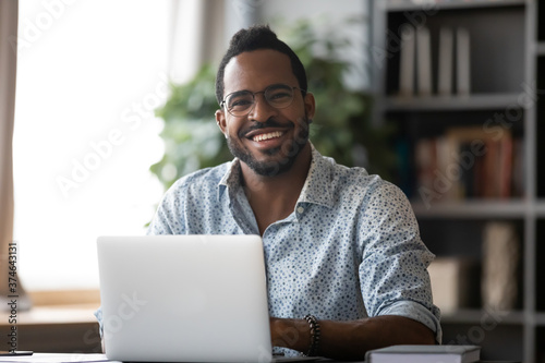 Foto Head shot portrait smiling African American businessman wearing glasses sitting