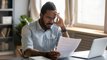 Stressed Dissatisfied African American Businessman Reading Letter With Bad News, Unexpected Debt, Bank Or Job Dismiss Notification, Student Working On Difficult Project, Holding Document In Hand