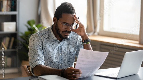 Stressed dissatisfied African American businessman reading letter with bad news, Fotobehang