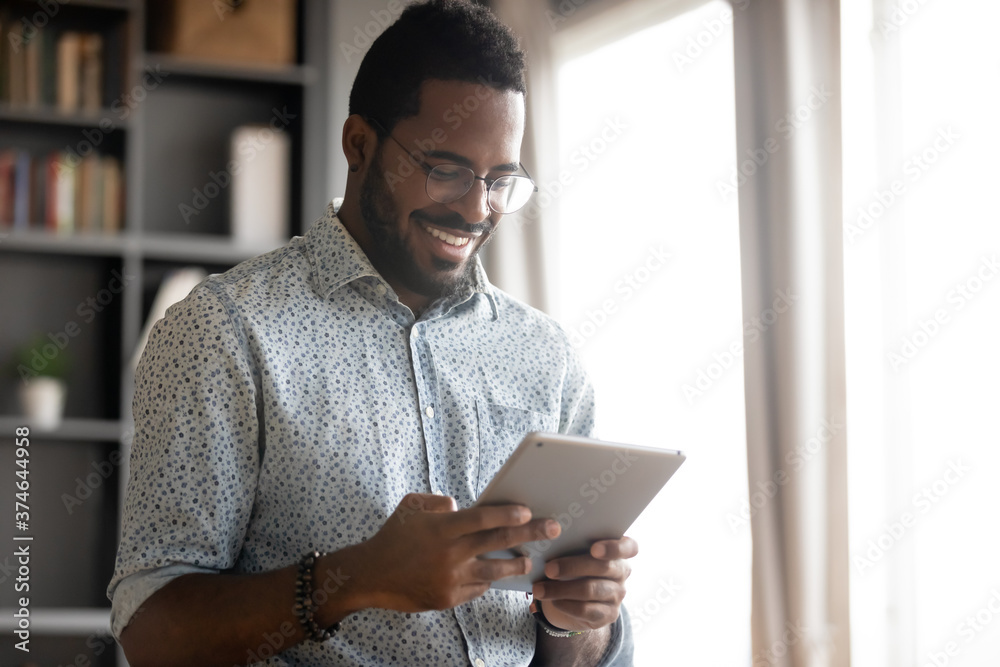Fototapeta Smiling African American man wearing glasses holding computer tablet, looking at screen, playing game, browsing apps, chatting with friends in social network, having fun with gadget close up