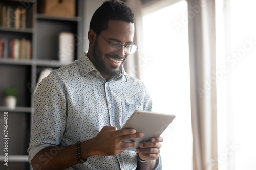 Fotografie, Tablou Smiling African American man wearing glasses holding computer tablet, looking at