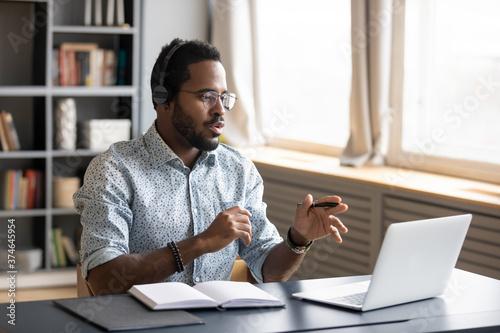 Fototapeta African American man wearing headphones speaking, using laptop, student wearing