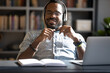 canvas print picture - Satisfied African American businessman wearing headphones enjoying music with closed eyes, relaxing during break, sitting at work desk, smiling young man wearing glasses listening to favorite song
