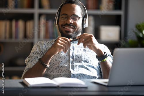 Obraz na plátne Satisfied African American businessman wearing headphones enjoying music with cl
