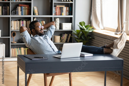 Fototapeta Smiling peaceful African American man resting, leaning back in office chair, sit