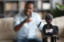 Close Up African American Blogger Using Digital Camera, Recording Vlog, Young Man Creating Content For Social Network, Business Coach Mentor Speaking, Shooting Lecture, Webinar Sitting On Couch
