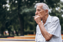 Senior Adult Men Smoking Cigarette Outdoors In The City  Park When Sitting On The Bench.