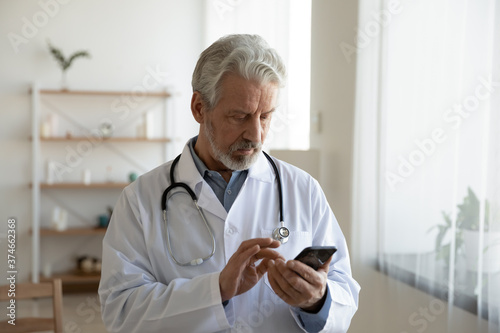 Fototapeta Serious focused mature doctor wearing white coat uniform with stethoscope using
