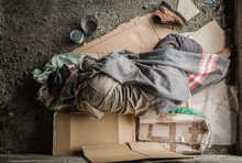 Old Homeless Man Wearing Sweater And Blanket Sleeping On Cardboard Seeking Help Because Hungry And Food Beggar From People Walking Pass On Street. Poor Man Homeless And Depression Concept.