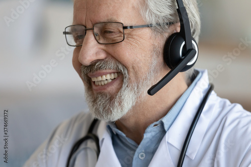 Close up head shot smiling mature doctor wearing headset working online, happy s Canvas
