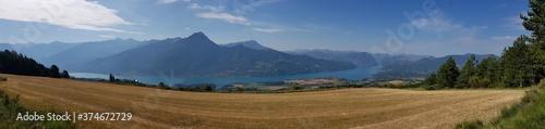 Panoramique : champs devant le lac et les montagnes