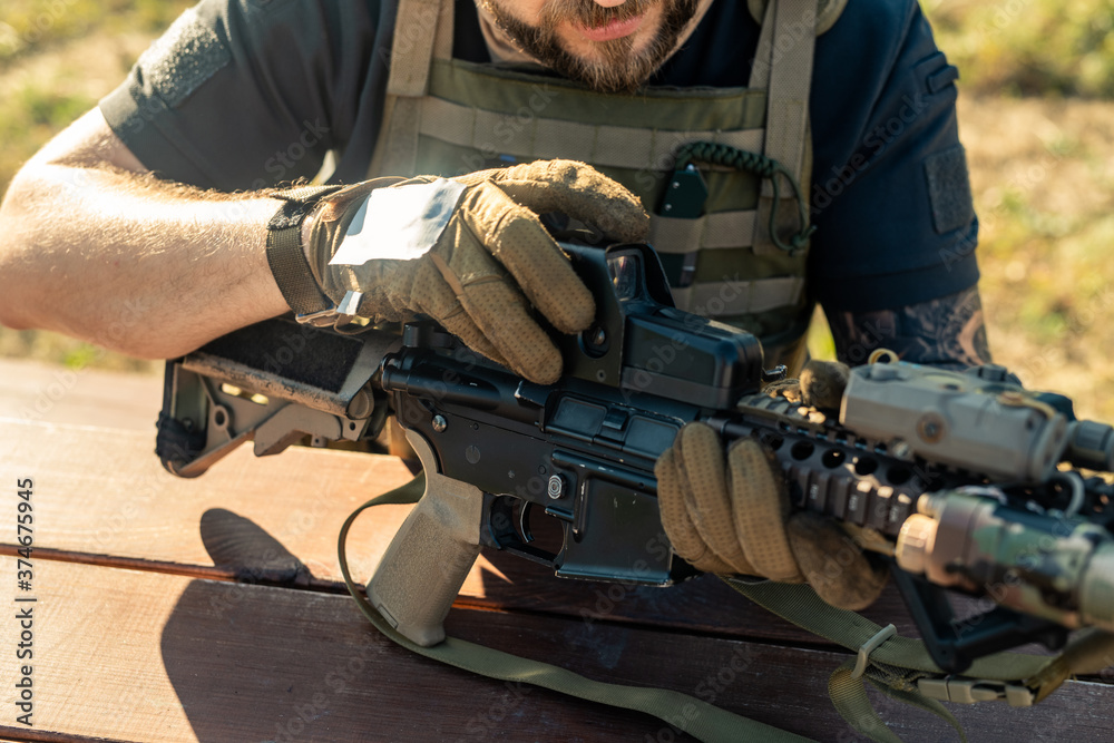 Fototapeta Close-up of bearded man in gloves sitting at table outdoors and assembling rifle