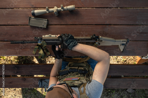 Above view of skilled young American man in gloves sitting at wooden table and assembling rifle while preparing for shooting #374676556