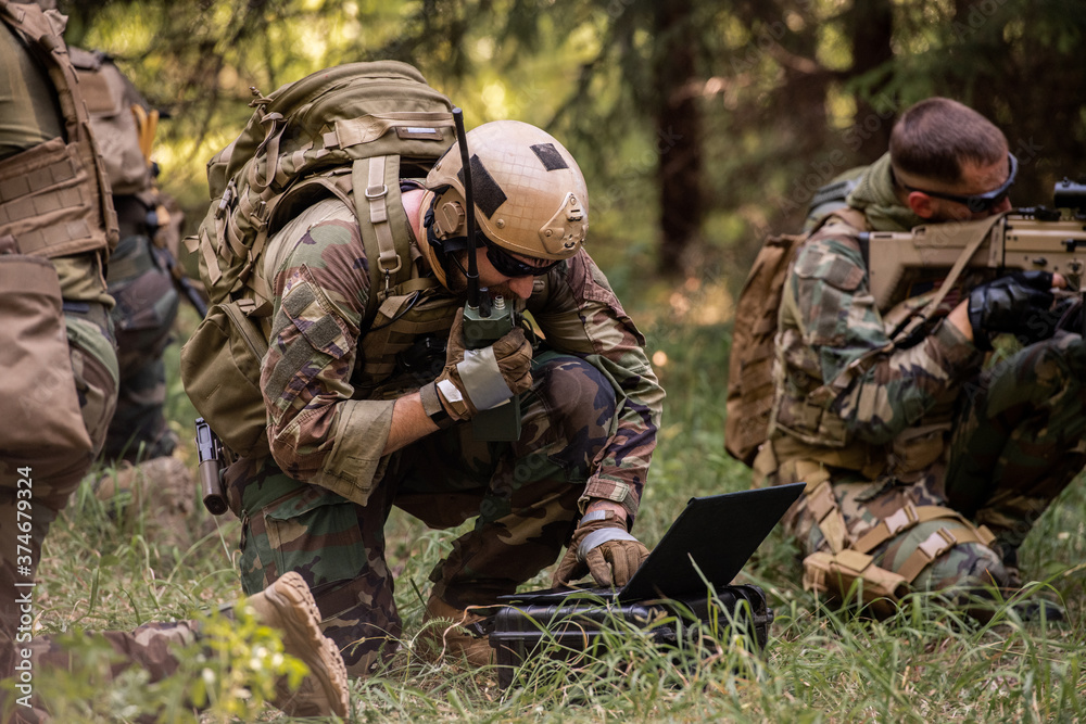 Fototapeta Busy soldier with backpack using military laptop while passing information through radio device in forest