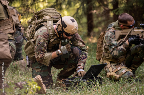 Busy soldier with backpack using military laptop while passing information through radio device in forest #374679324