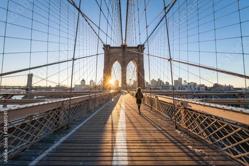 Fototapety, obrazy: Woman walking across the Brooklyn Bridge at sunrise, New York City, USA