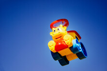 Children's Toy Little Train Close Up. Saturated Bright Children's Toy. Yellow Toy Train With Blue Sky