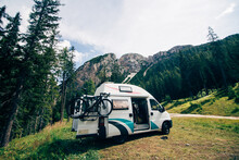 Cute Vintage Camper Van Or Camping RV Parked In Wild Camping Spot In Mountain Forest. Bicycle On Bike Rack Parked Next To Converted Van. Life On The Road In Van, Outdoor Nomadic Lifestyle