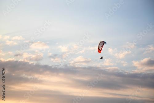Parapente volant dans la lumière du soir sur un fond de nuages éclairés par les Tableau sur Toile