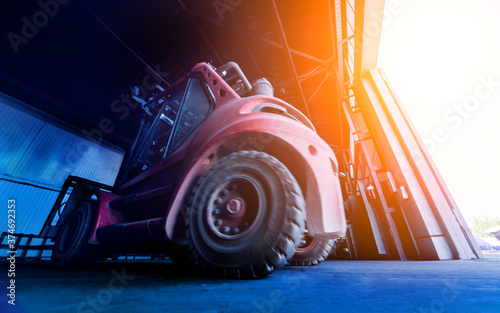 Fotografie, Obraz The big industrial forklift drives into the warehouse.