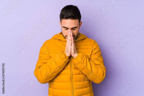 Young caucasian man isolated on purple background praying, showing devotion, religious person looking for divine inspiration Wallpaper Mural