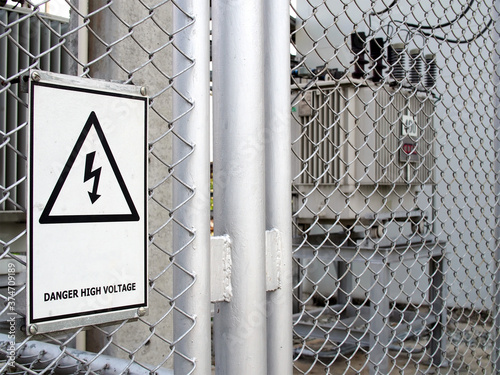 Valokuva warning sign hanging on gray wire mesh fence that surrounds transformer electric