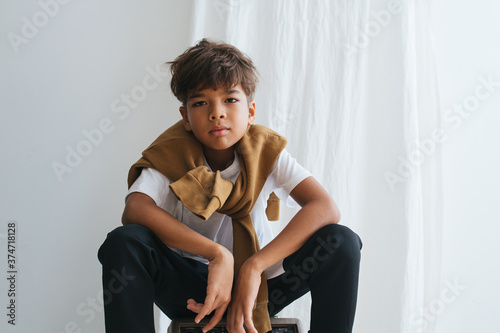 Emotionless indian asian kid looking at the camera, sitting low, knees up Fototapet