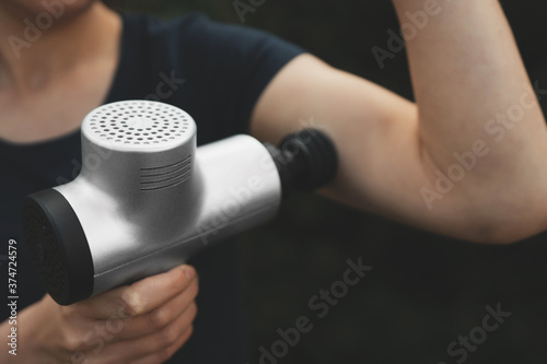 Fototapeta Woman massaging his hand with massage percussion device after workout