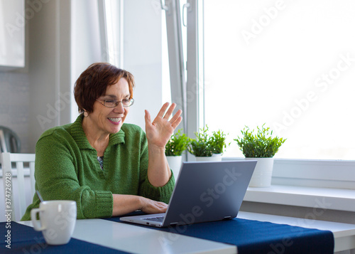 Portrait of a senior woman having online conversation Fotobehang